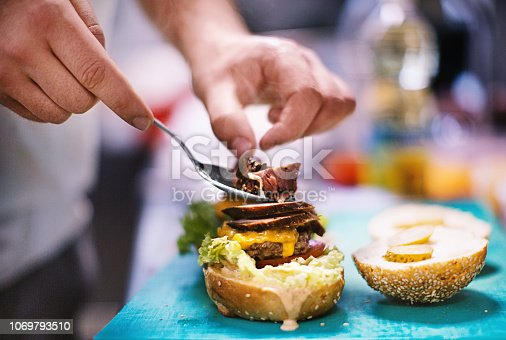 Unrecognizable chef preparing delicious burger. He is putting last piece of meat with a spoon. Burger is almost ready.