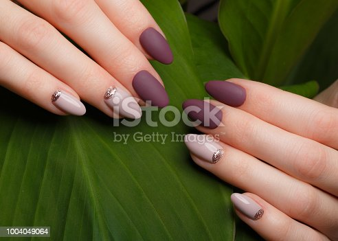 istock Tender neat manicure on female hands on green leaves background. Nail design 1004049064