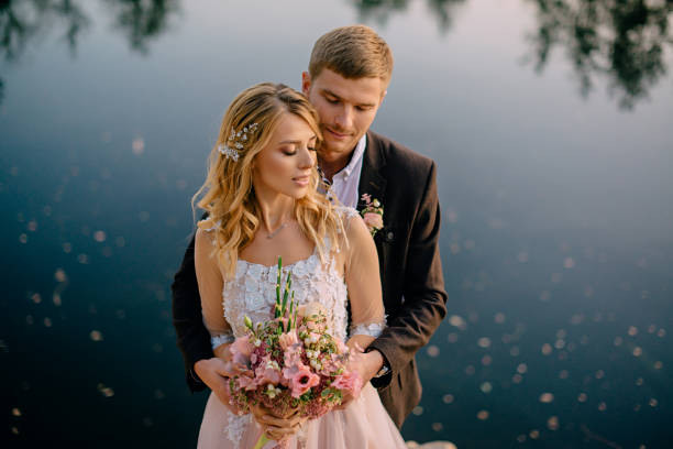 tender portrait of the newlyweds at sunset stock photo