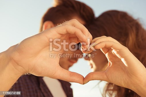 950598260 istock photo Tender sweet couple in love gesturing a heart with fingers 1139074169
