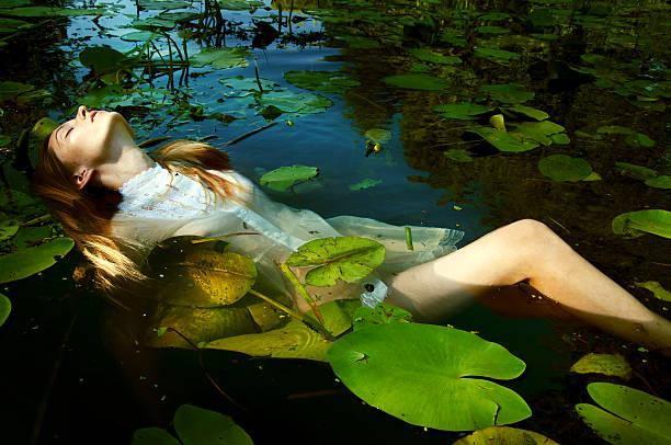 zarte junge frau schwimmen unter wasser lilien - teichfiguren stock-fotos und bilder
