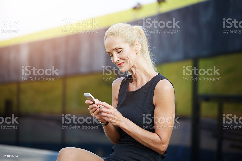 Tendered woman texting friends stock photo