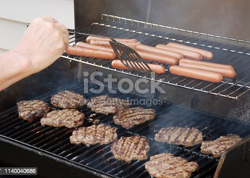 Closeup of a backyard BBQ with hamburgers and hot dogs.