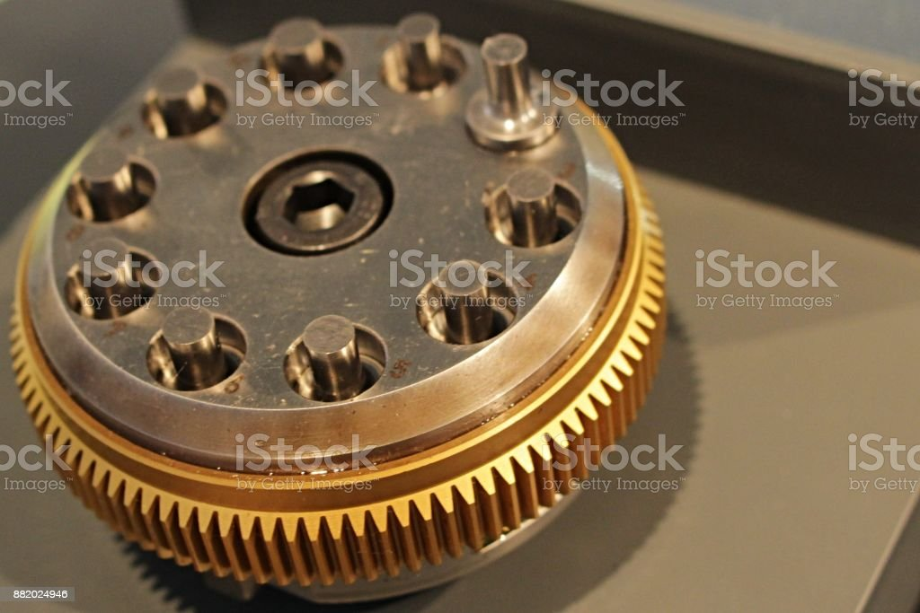 Tenfold multitool used in compression molding and punching machines with cog wheel around the diameter displayed on industrial and machinery expo stock photo