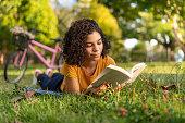 istock Tenn girl reading a book lying on the grass 1264573507