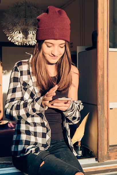 tenn girl using smartphone on a window's home - modefarben sommer 2016 stock-fotos und bilder