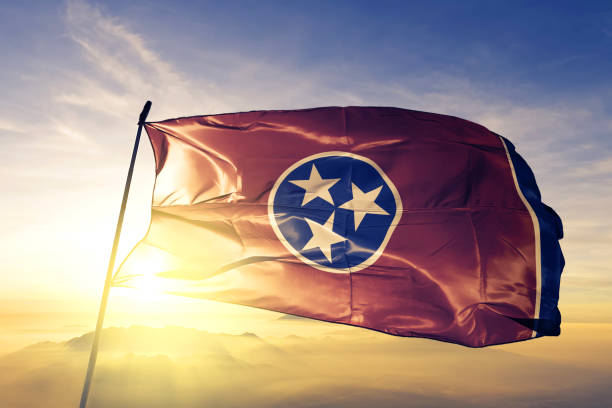 Tennessee state of United States flag textile cloth fabric waving on the top sunrise mist fog stock photo
