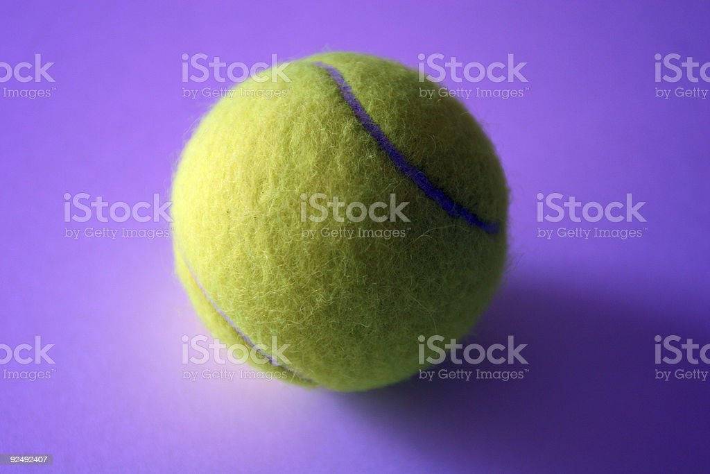 Tennis ball against purple background (shallow DOF) royalty-free stock photo