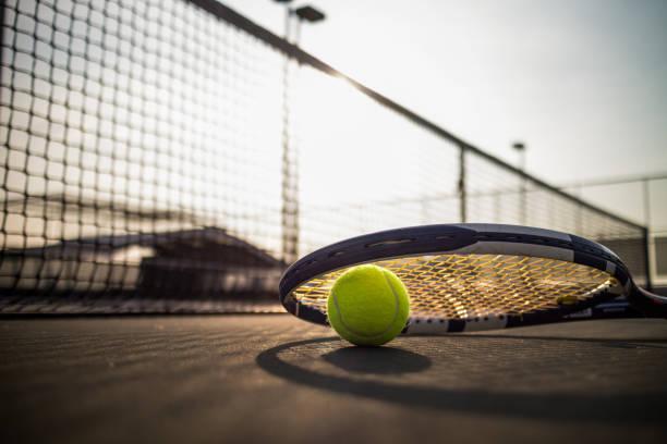 pelota de tenis y raqueta en cancha dura bajo la luz solar - tenis fotografías e imágenes de stock