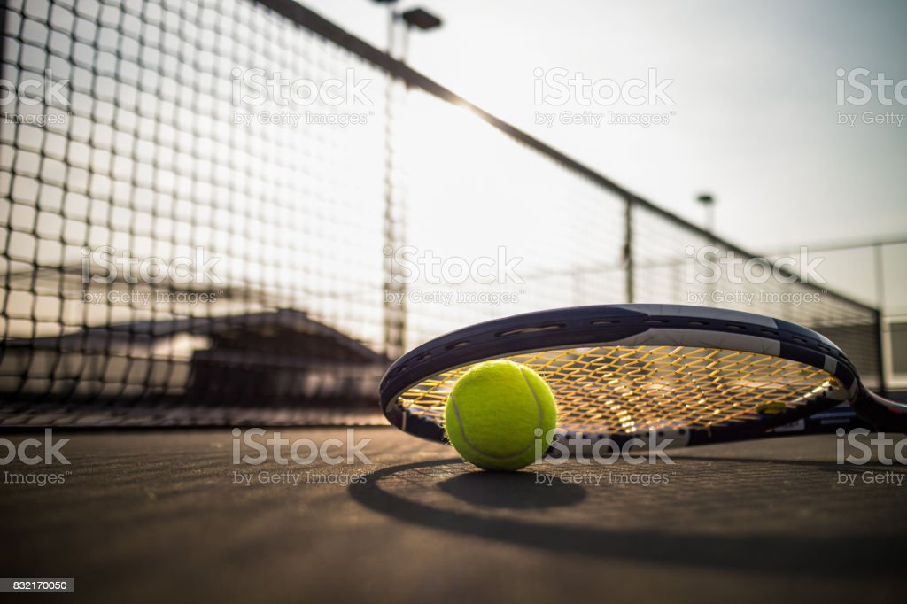 Tennis ball and racket on hard court under sunlight stock photo