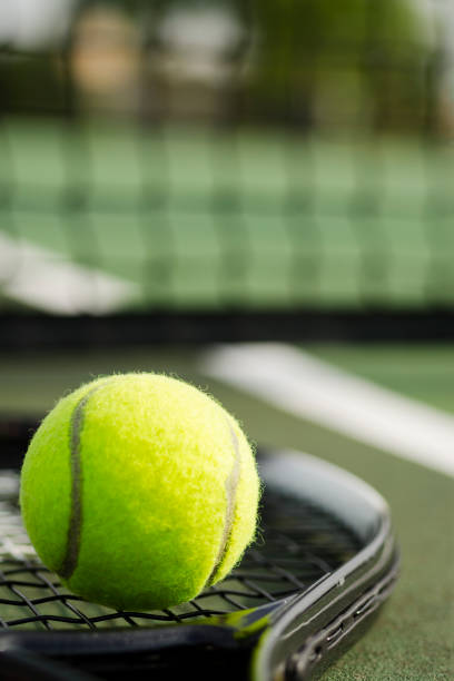Tennis Ball and Racket on the Court Vertical stock photo
