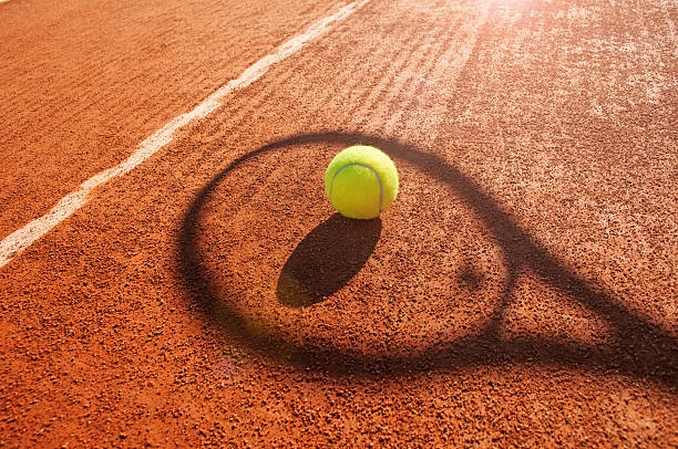 tennis ball and racket shadow on  clay court - racket stock pictures, royalty-free photos & images
