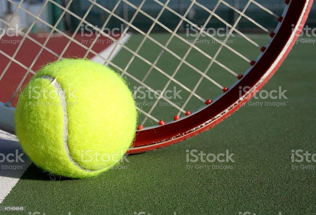 Tennis ball and racquet on a green tennis court stock photo