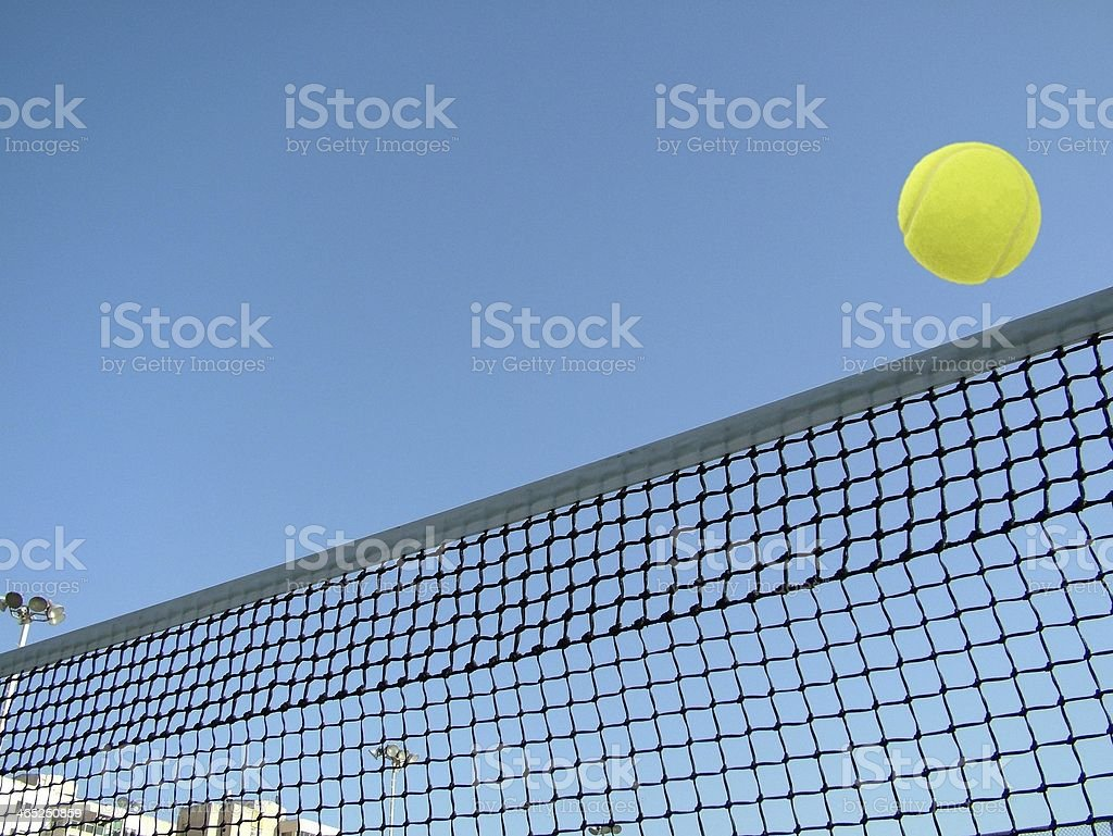 Tennis ball flying over net  on blue sky background. royalty-free stock photo