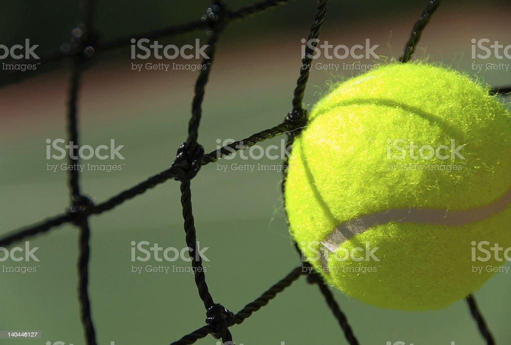 Tennis ball hitting net on court royalty-free stock photo
