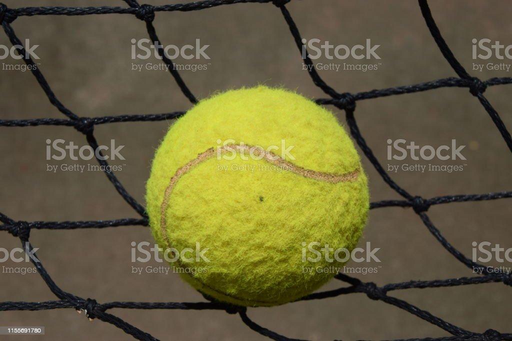 Tennis ball hitting the net on court closeup match sport game set