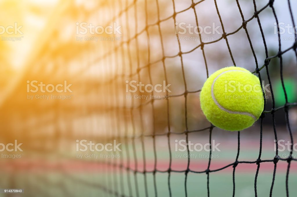 Tennis ball hitting to net on blur court background stock photo