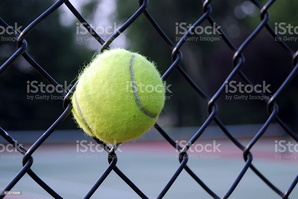 Tennis Ball in fence royalty-free stock photo
