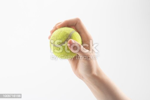 istock Tennis ball in hand isolated 1009716156