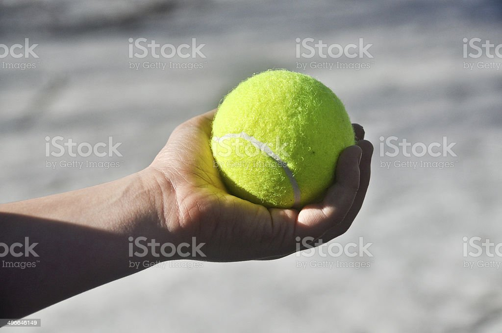 Tennis ball in his hand. stock photo