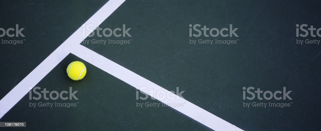 Tennis Ball Lying on Court stock photo