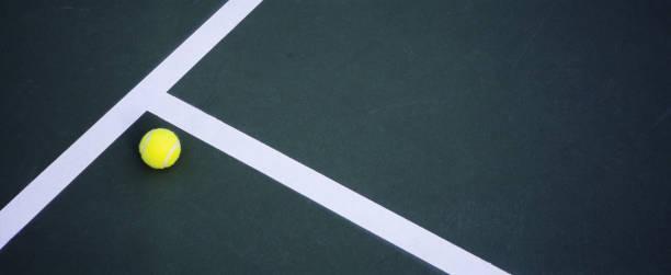 Tennis Ball Lying on Court stock photo