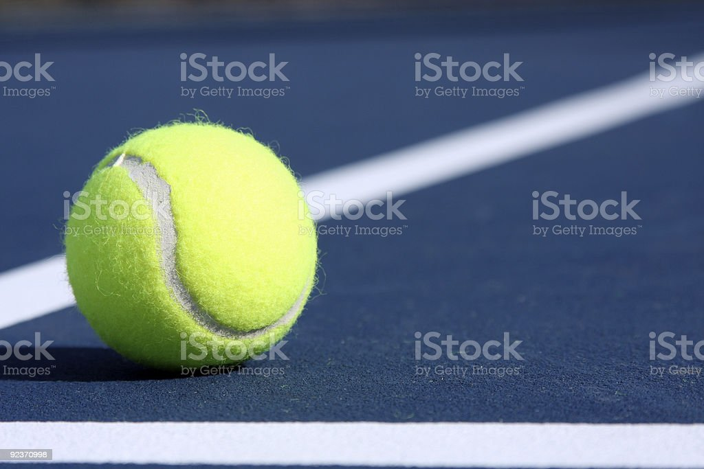 Tennis Ball on a Blue Outdoor Court royalty-free stock photo
