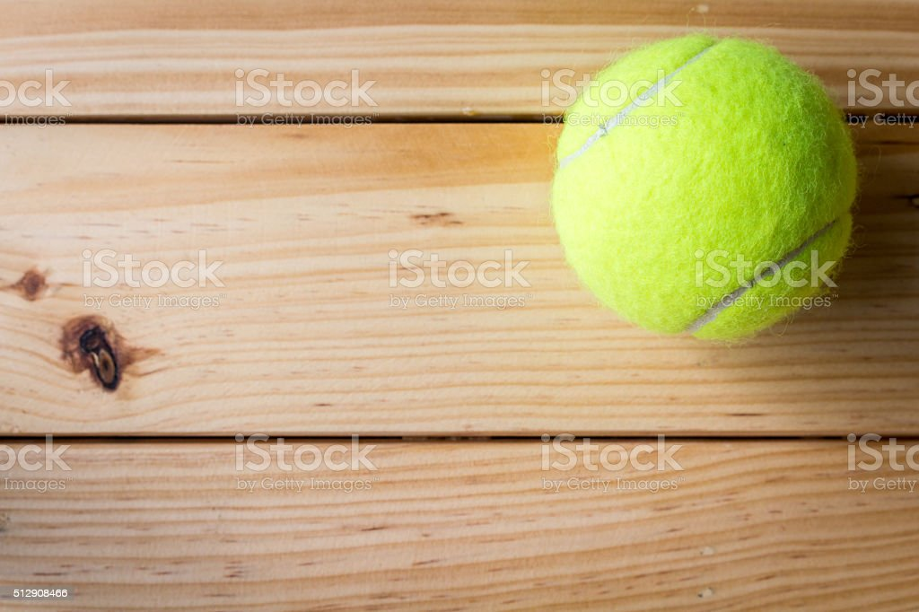 Tennis ball on a wooden table stock photo