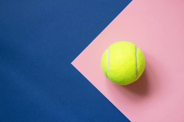 Balle de tennis sur fond de papier bleu et rose. Sport concept. Espace copie - Photo