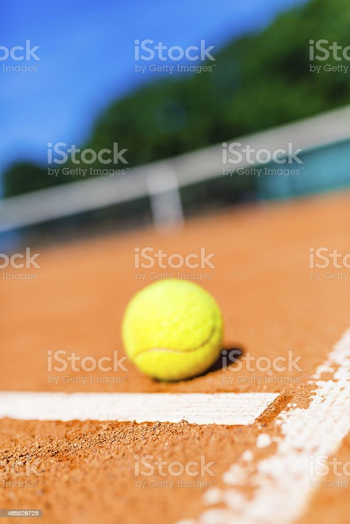 Tennis ball on clay court royalty-free stock photo
