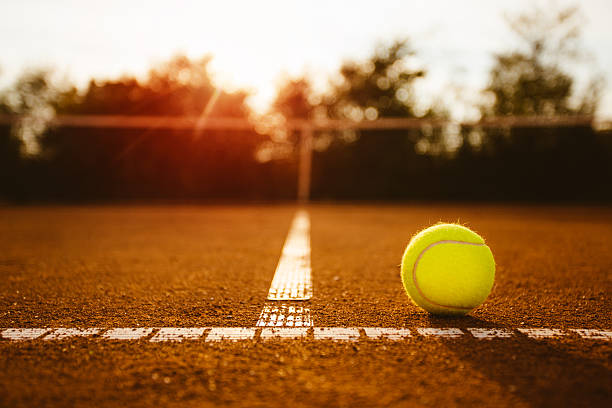 tennis ball on clay court - tennis stock photos and pictures