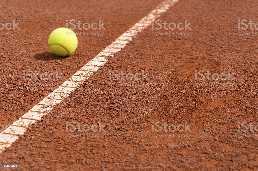 Tennis ball on clay with a footprint stock photo