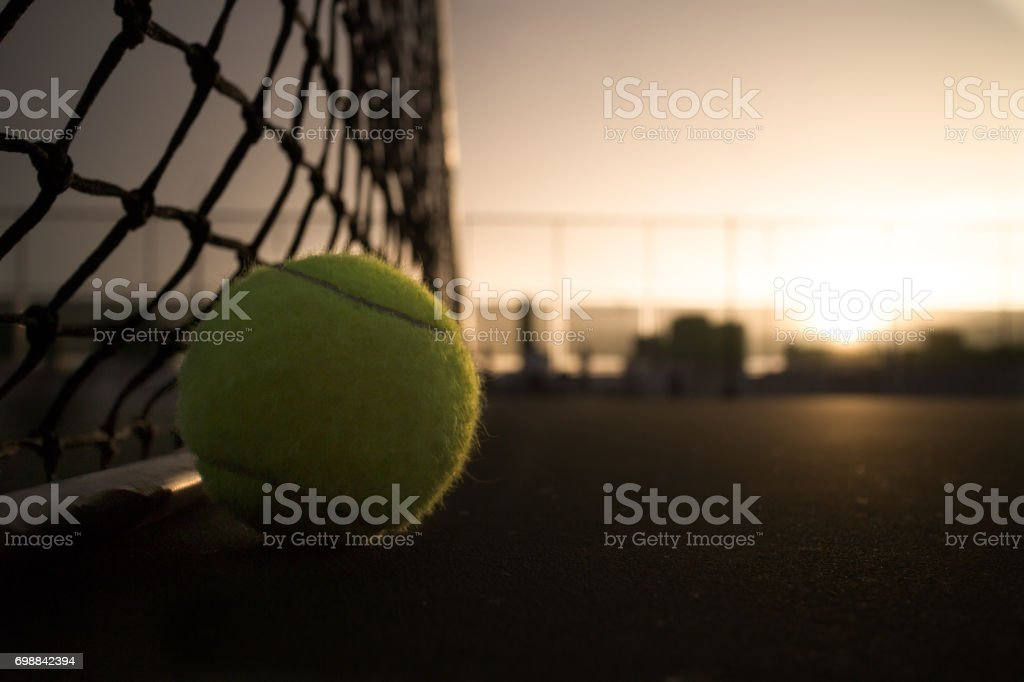 Tennis ball on court at dawn time stock photo