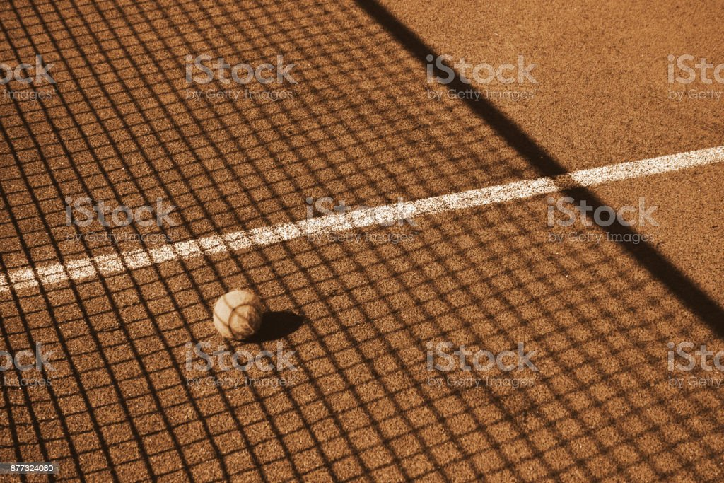 Tennis ball on court in the shade setkey. A textured background.Copy paste place stock photo