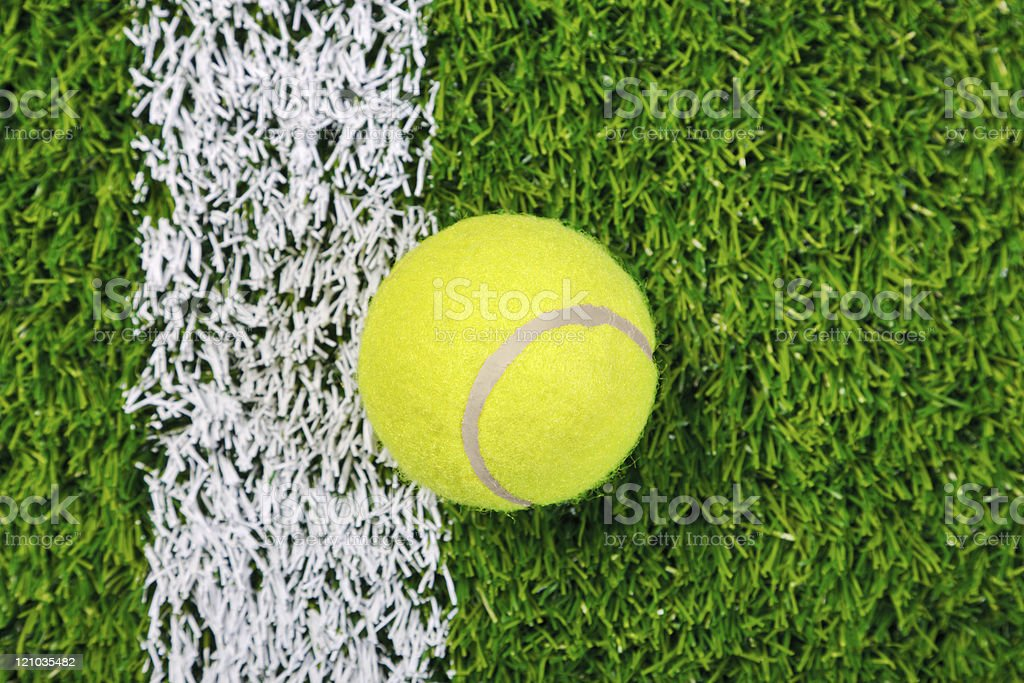 Tennis ball on grass from above. stock photo