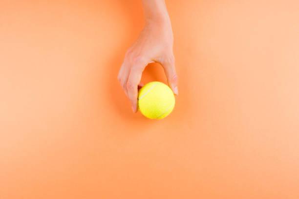 Tennis ball on orange in woman's hands stock photo