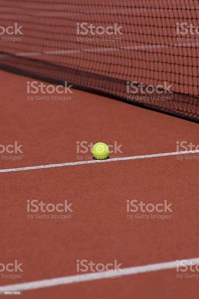 Tennis ball on red field royalty-free stock photo
