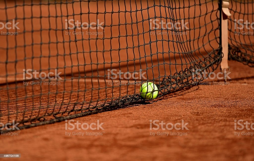 Detail shot with a tennis ball close to the net on a tennis clay court