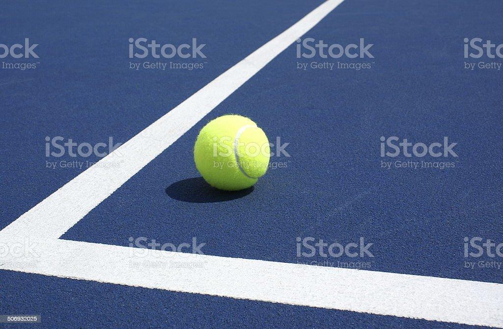 Close up of tennis ball on blue tennis court