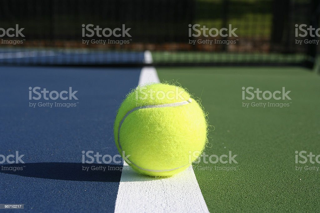 Tennis Ball on the Court with Net in background stock photo
