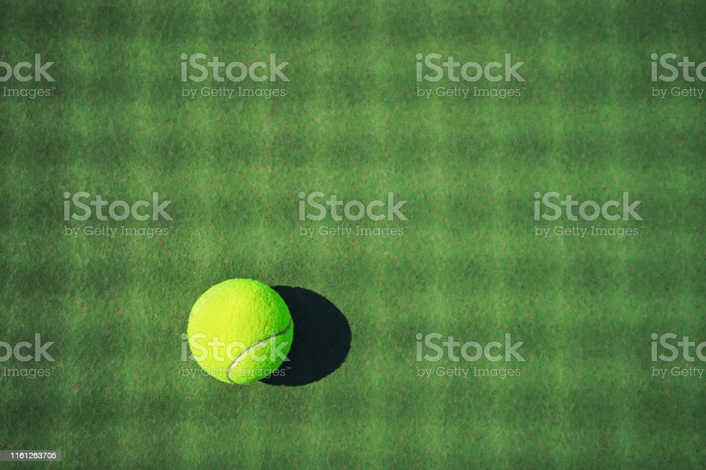 Tennis ball on the green court with net shadows. Concept of sport,...