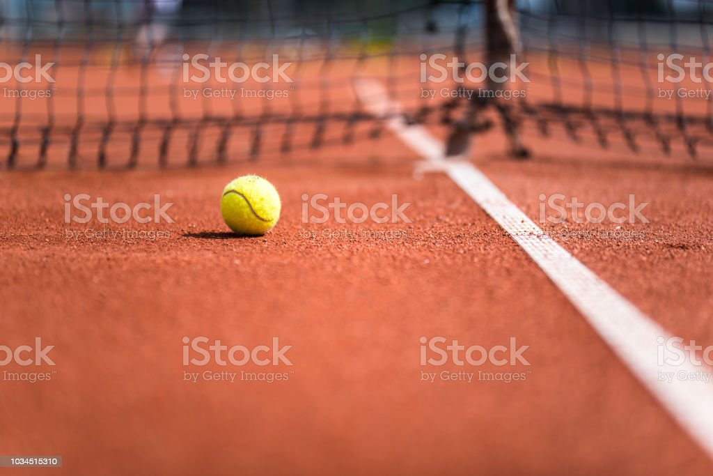 Close up of a tennis ball on the orange ground by the white stripe.