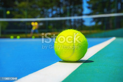 1153628111istockphoto Tennis ball on white court line on hard modern blue green court with player, net, balls, trees on the background. 1156512648