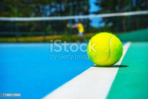 1153628111istockphoto Tennis ball on white court line on hard modern blue green court with player, net, balls, trees on the background. 1156512653