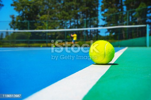 1153628111istockphoto Tennis ball on white court line on hard modern blue green court with player, net, balls, trees on the background. 1156512687