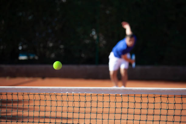 Tennis Ball Over the Net After First Serve Hitting stock photo