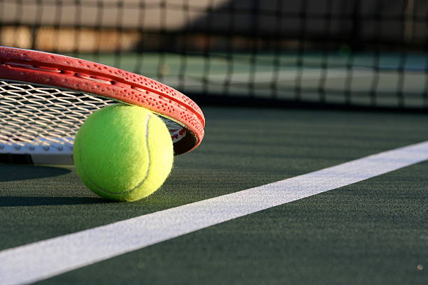 Tennis Ball & Racket on a Green Outdoor Court stock photo