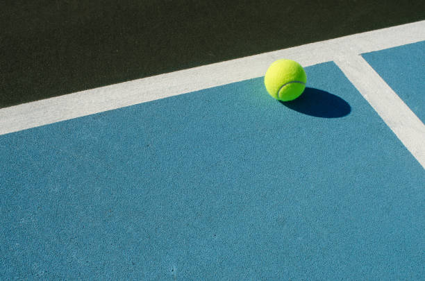 tennis ball rests on blue tennis court - tennis stock pictures, royalty-free photos & images