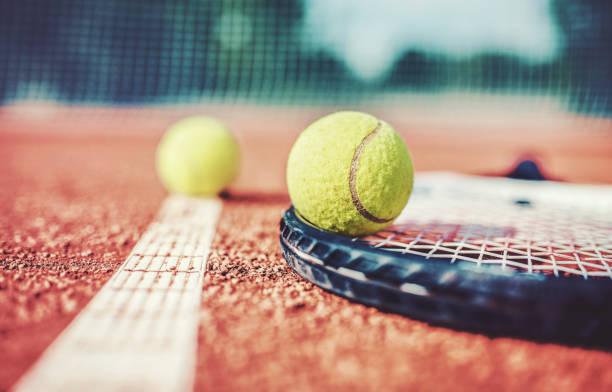pelota de tenis con la raqueta en la cancha de tenis. deporte, concepto de recreación - tenis fotografías e imágenes de stock
