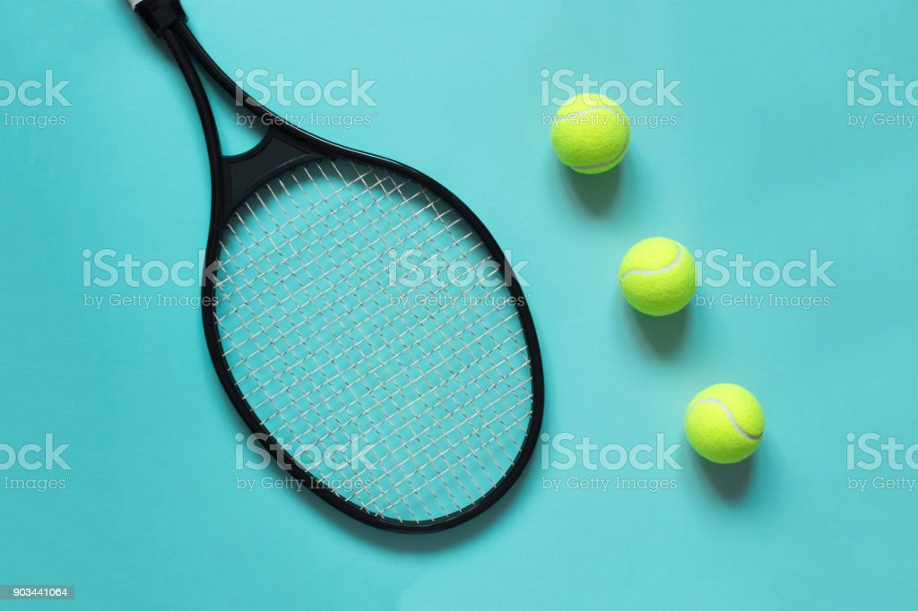 Tennis balls and racket on blue background. Concept sport. Flat lay.